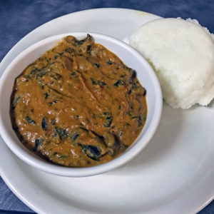 Funmi's mushroom peanut-tomato stew with spinach and tuwo cornflour meal.