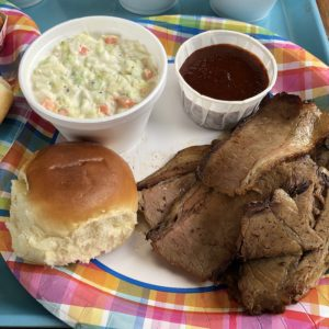 Holy Smokes' thin-sliced, smoky brisket with creamy slaw, a dinner roll, and sweet-hot tomato-based sauce.