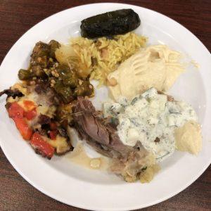 Pulled chunks of Al Hamra's whole roast lamb are surrounded by a stuffed grape leaf, okra, rice, hummus, yogurt-cucumber mix, and tomatoes, eggplant and lamb.