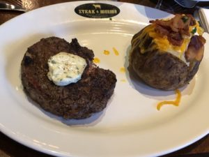 Steak & Bourbon's 14-ounce Certified Angus rib eye steak and loaded baked potato.