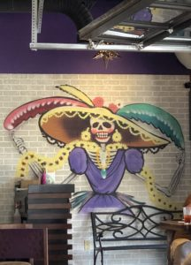 La Catrina, an iconic figure of the Day of the Dead, is prominently featured in murals at the restaurant that bears her name.