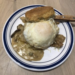 Biscuit Belly's Edgy Veggie stacks an egg, cheese, and fried green tomato on an oversize biscuit bathed in thick mushroom gravy.