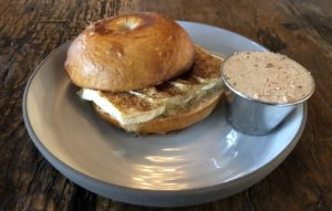 A light, crisply crusted bagel at Butchertown Grocery Bakery bears slices of brie, crushed pecans, and seasonal autumn spice.