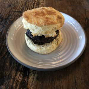 A lofty biscuit the size of a hockey puck makes a sandwich with hot-and-spicy sausage at Butchertown Grocery Bakery.