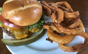 Shady Lane's Brownsboro burger, plated and ready to eat, with a side of onion rings.