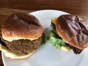 Two meatless BurgerIM specialties, a burger-size falafel and an Impossible Burger.