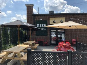 MexA Steak Tacos has set up a spacious patio area with picnic tables and umbrellas on part of its parkling lot behind the building.