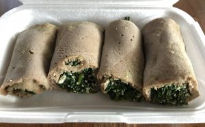 The kosta wrap appetizer at Queen of Sheba fills rolls of injera with sauteed fresh spinach, onions, garlic, and house-made aybe (house-made cottage cheese).