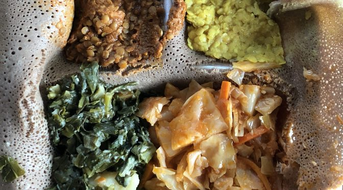 The veggie combination at Queen of Sheba tops injera with two colors of lentil misir wot, atakilt and gomen wot.
