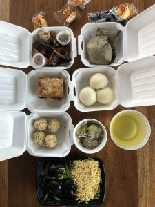 A selection of takeout dim sum from Jade Palace, neatly packed in white plastic foam boxes, fills our dinner table.