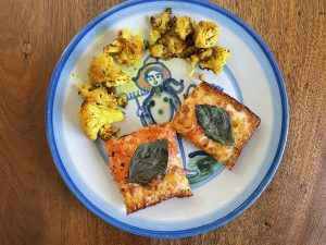 A couple of squares of vodka pizza and a serving of roasted turmeric cauliflower look right at home on an iconic Louisville Hadley Pottery plate.