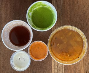 A colorful selection of chutneys and a tub of sambar soup accompany our takeout meal from Shreeji.