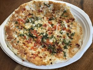 Shreeji's tomato chili onion uttapam looks a lot like a pizza, but it's full of robust Indian flavors built on a thin rice and lentil cake.