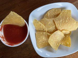 Crackling crisp, freshly fried tortilla chips and mild but tomato-rich salsa at Taco Choza.