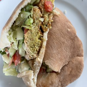 We've carved an Alwatan falafel in half to display its generous filling of tender falafel balls, lettuce, tomato, and creamy tzatziki sauce in a fresh, tender pita.