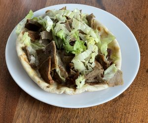 The gyros at Alwatan is loaded with chunks of rough-sliced beef-lamb gyros meat, lettuce, tomato, and tzatziki on a grilled fresh pita.