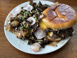 Hog Father's thin, crisp-cooked smash burger is built with tasty toppings on a potato bun.
