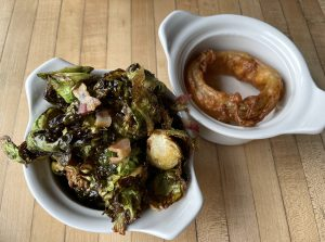 Side dishes at Monnik: earthy, savory brussels sprouts and bacon, and a huge single onion ring.
