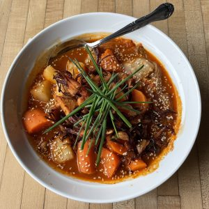 Jjigae is a hearty, spicy Korean dish of hot-sour broth filled with carrots, potatoes, and fiery kimchi. Monnik makes it a veggie dish with jackfruit filling in for meat.