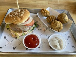 The new aloo tikki burger at BurgerIM puts a meatless Indian patty of potatoes, peas, and carrots into the more familiar setting of lettuce, cheese, onions, and tomatoes on a sesame seed bun.