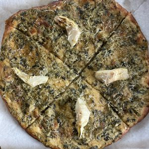 A 10-inch spinach-artichoke pizza is built on a wheat crust, with fresh artichokes and persuasively cheesy vegan cheeses.