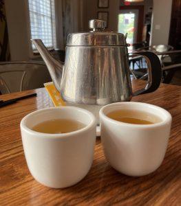 Clear, light jasmine tea with simple, handleless white cups.