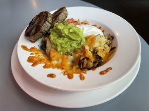 Home fries, two cheeses, guacamole and salsa make Le Suerte's potato melt a filling brunch plate, with a pair of breakfast sausages on the side.