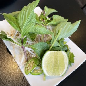 In traditional Vietnamese style, a pile of fresh greens, herbs, and hot peppers accompanies every bowl of pho.