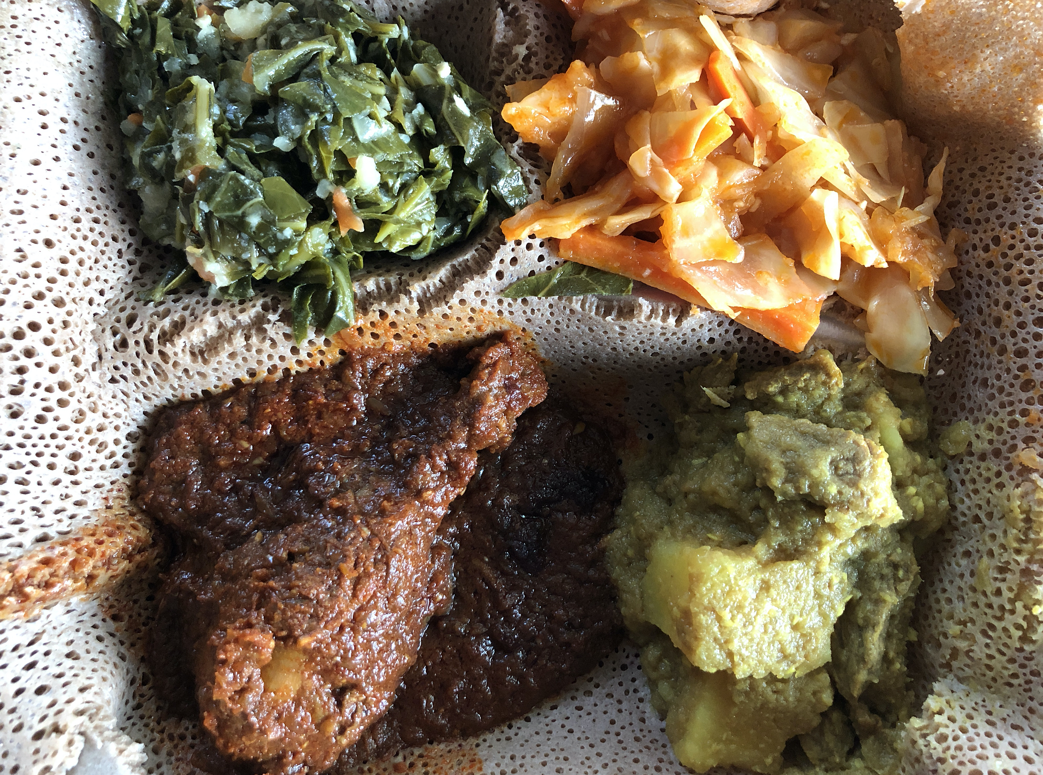 Queen of Sheba's meat and vegetable combination includes chicken doro wot, beef alicha sega wot, collards gomen wot and cabbage atakilt on a base of injera flatbread.